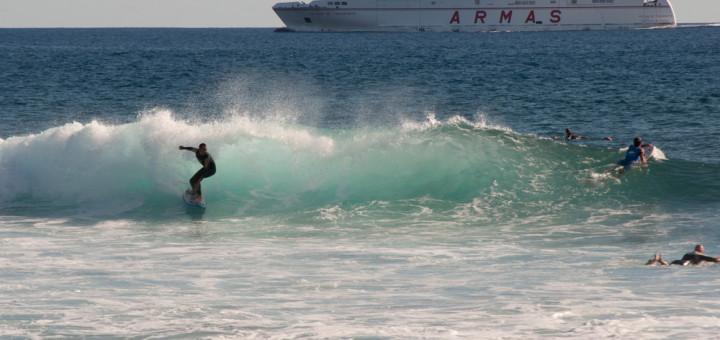 Practicando surf con un trasatlántico de fondo. ©El Viajar es un Placer