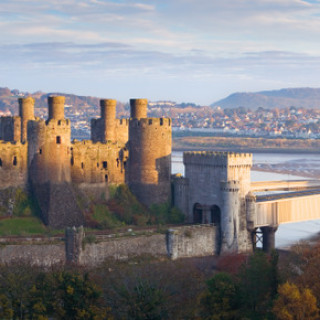 Conwy Castle is a large medieval fortification, on the coastline of North Wales, founded in the late 13th century. It overlooks the River Conwy estuary. Sunset.