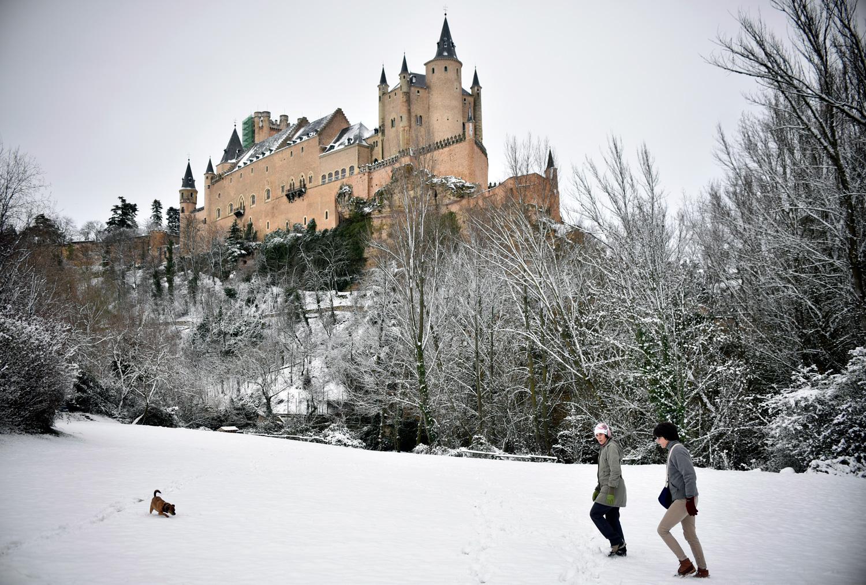 Dos personas y su perro disfrutan de la nieve bajo el Alcázar©El Viajar es un Placer